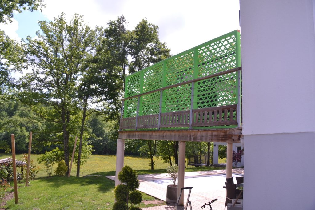 Paravent en bambou peint intégré à un jardin verdoyant - bambou créations
