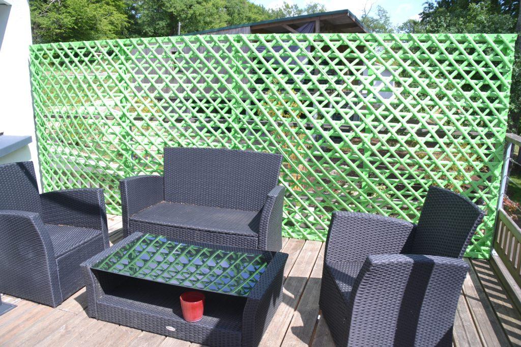 Paravent en bambou design peint sur une terrasse derrière un salon de jardin - bambou créations
